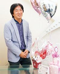 商品力と顧客満足の向上に注力する北川英明社長と看板商品のひとつバルーン電報。